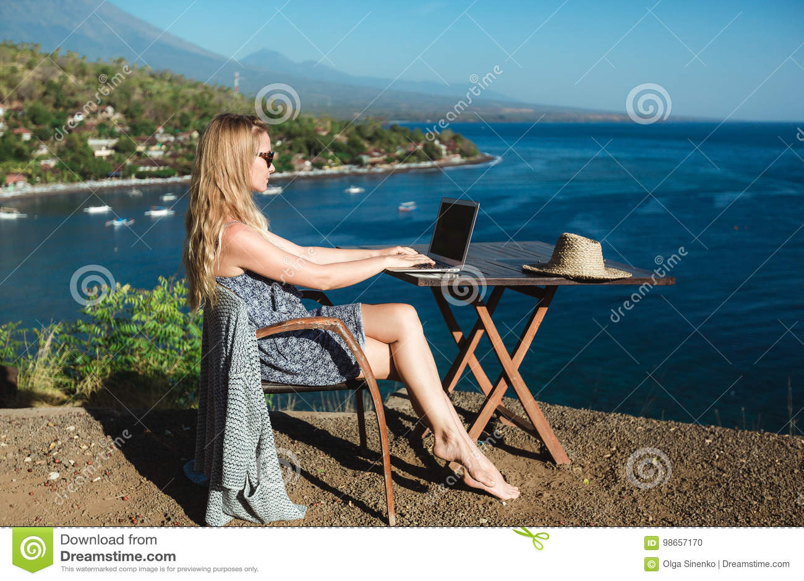 Kvinnligt arbete med hennes bärbar dator nära havet