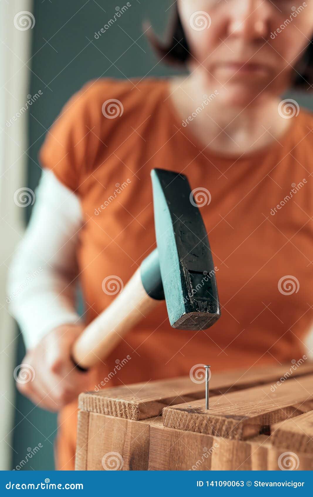 Kvinnligt bulta för snickare spikar in i träspjällådan