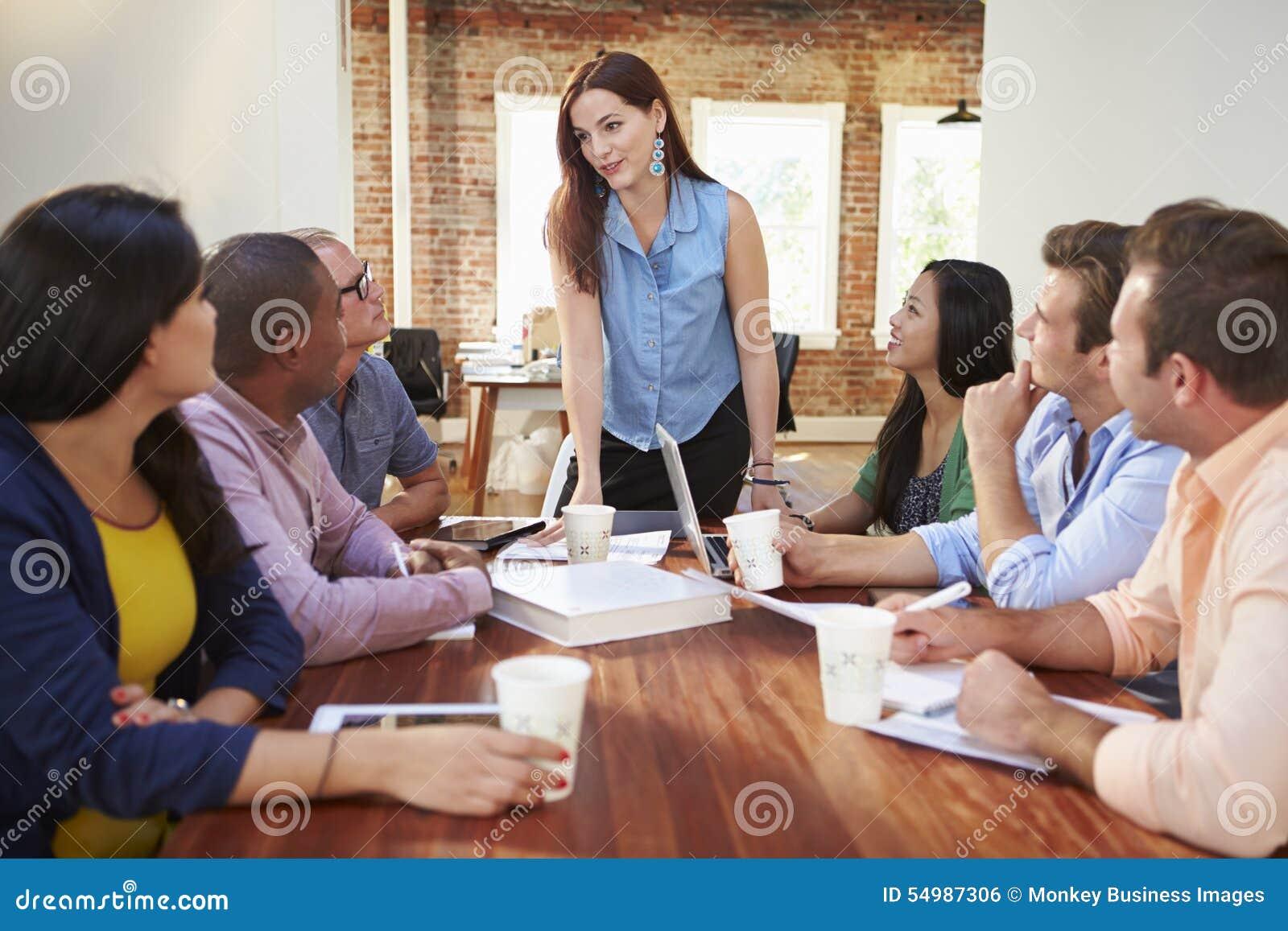 Kvinnligt framstickande Addressing Office Workers på mötet