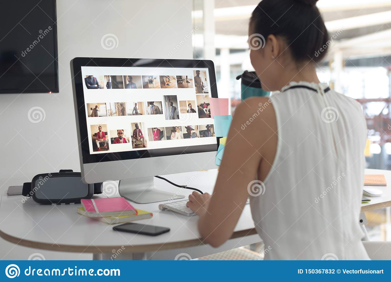 Kvinnligt grafiskt märkes- dricksvatten, medan arbeta på datoren på skrivbordet i ett modernt kontor
