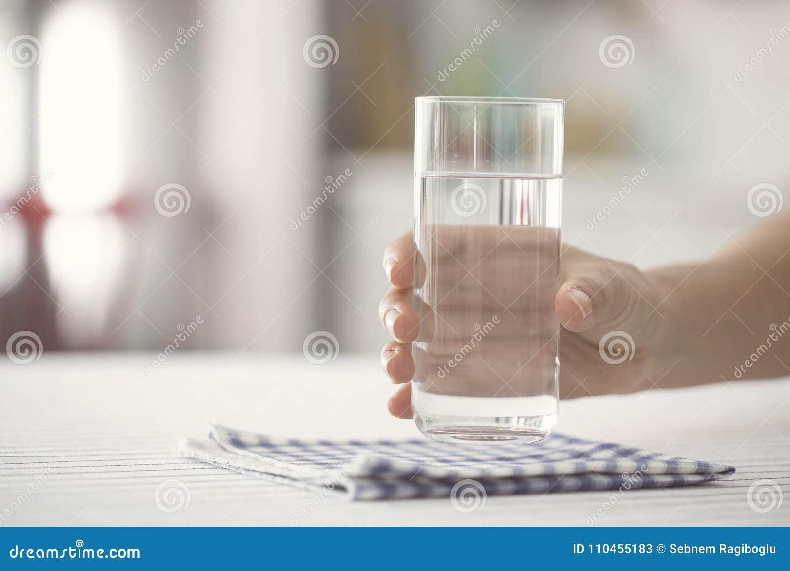 Kvinnligt hållande exponeringsglas av vatten kicthen på tabellen