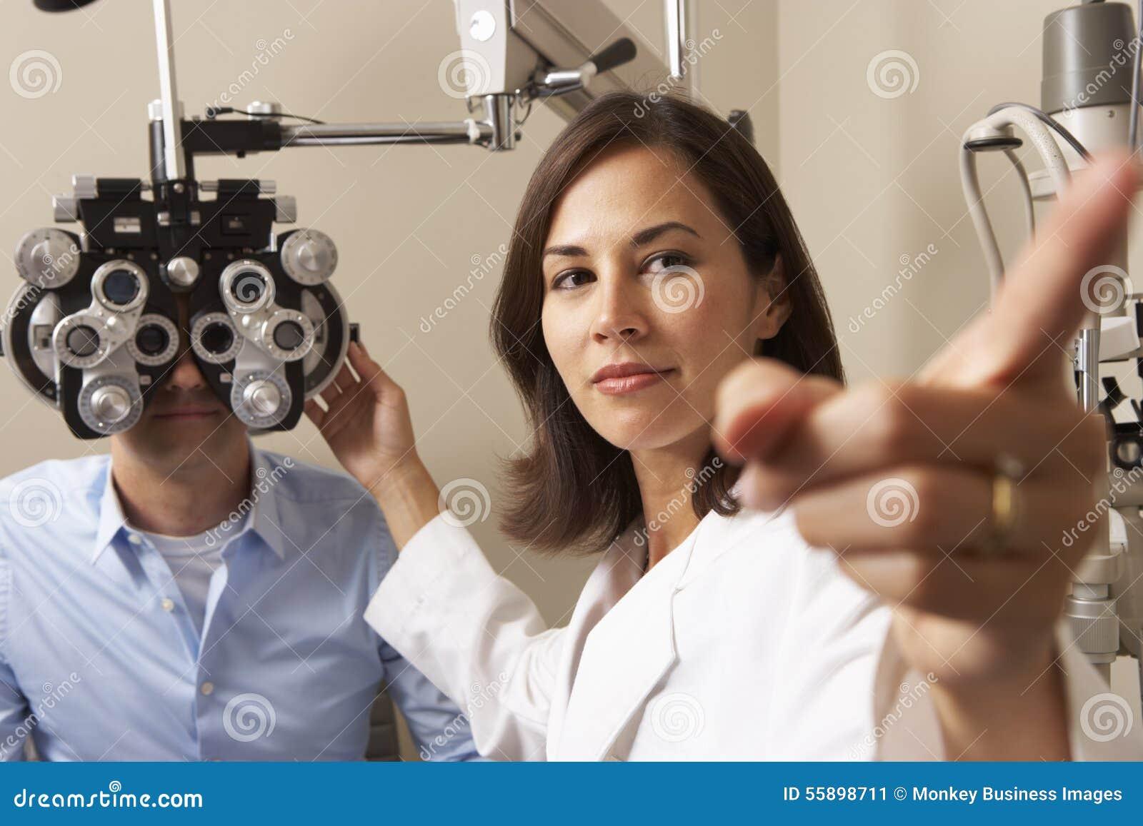 Kvinnligt prov för öga för optikerIn Surgery Giving man