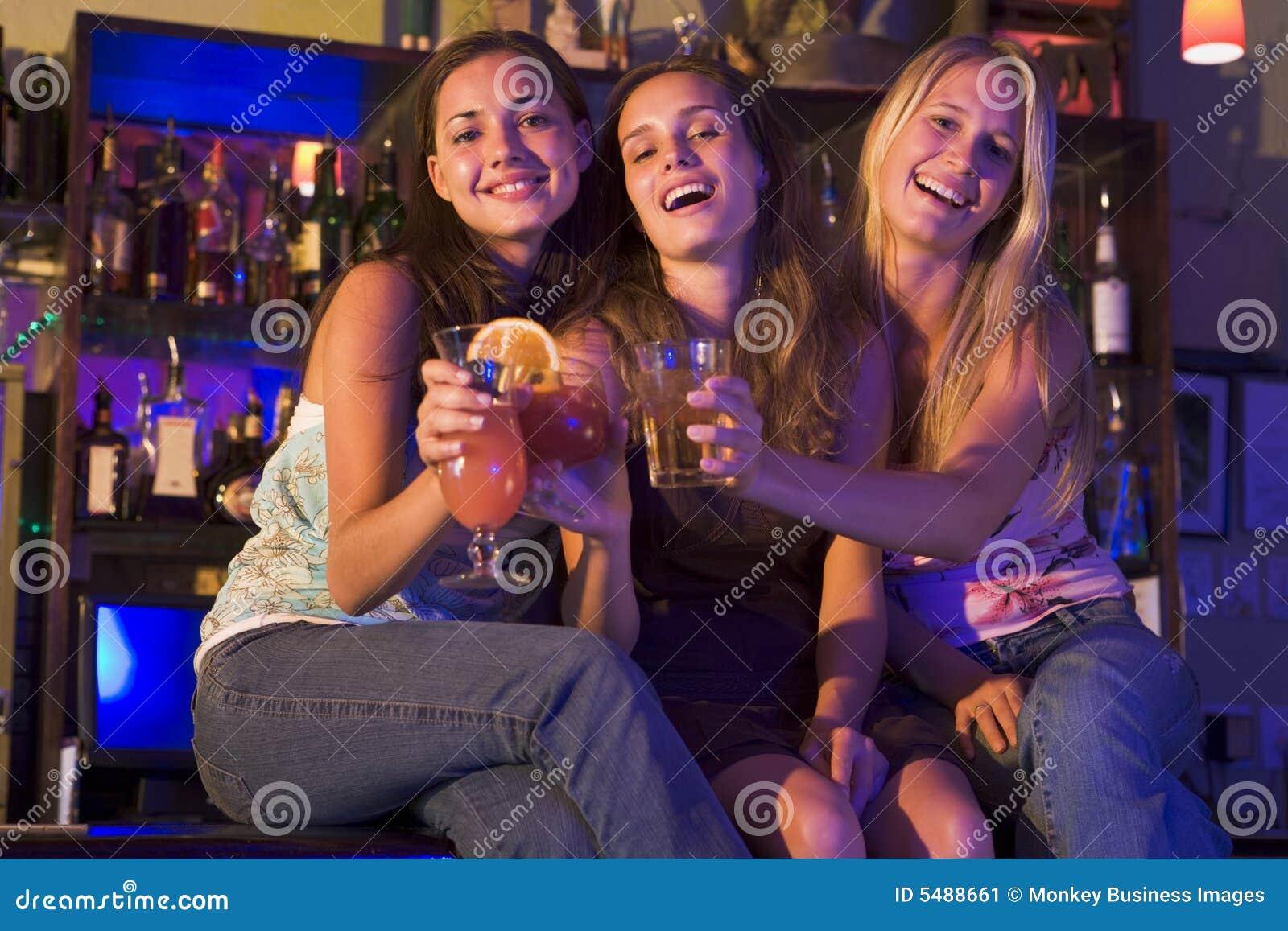 Kvinnor för sitting tre för stång unga counter