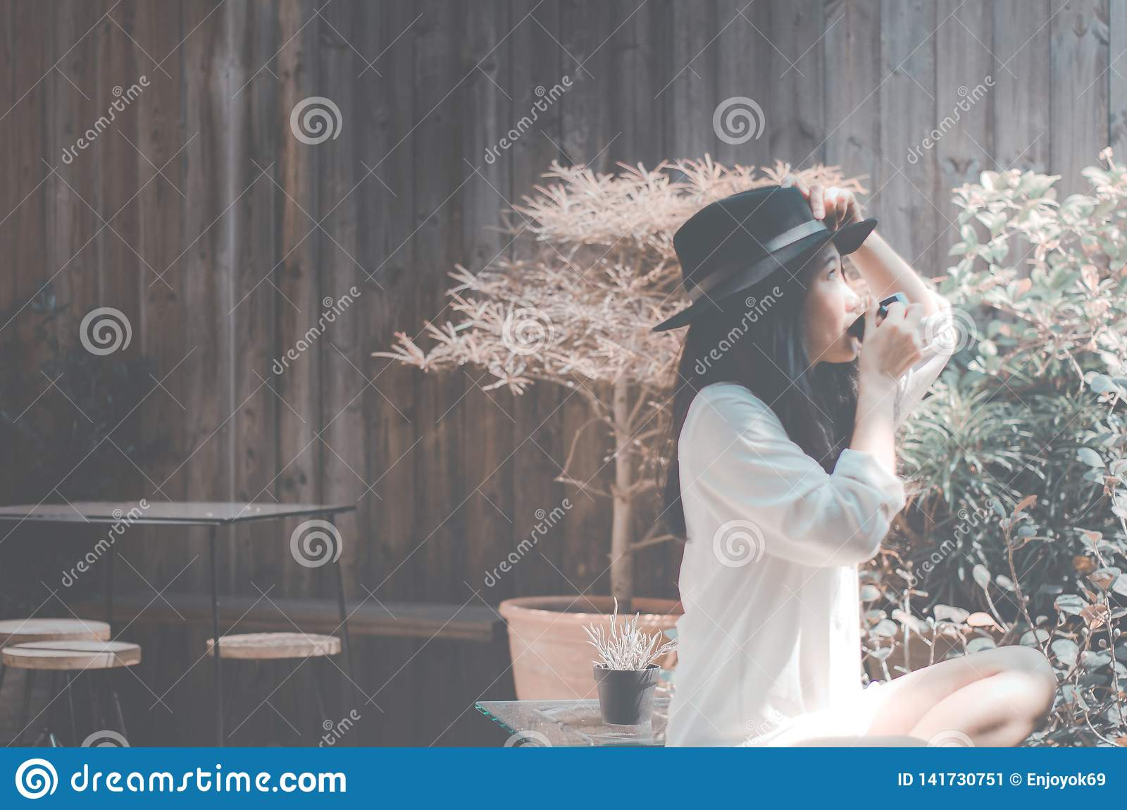 Kvinnor i trädgården i morgonen som dricker kaffe