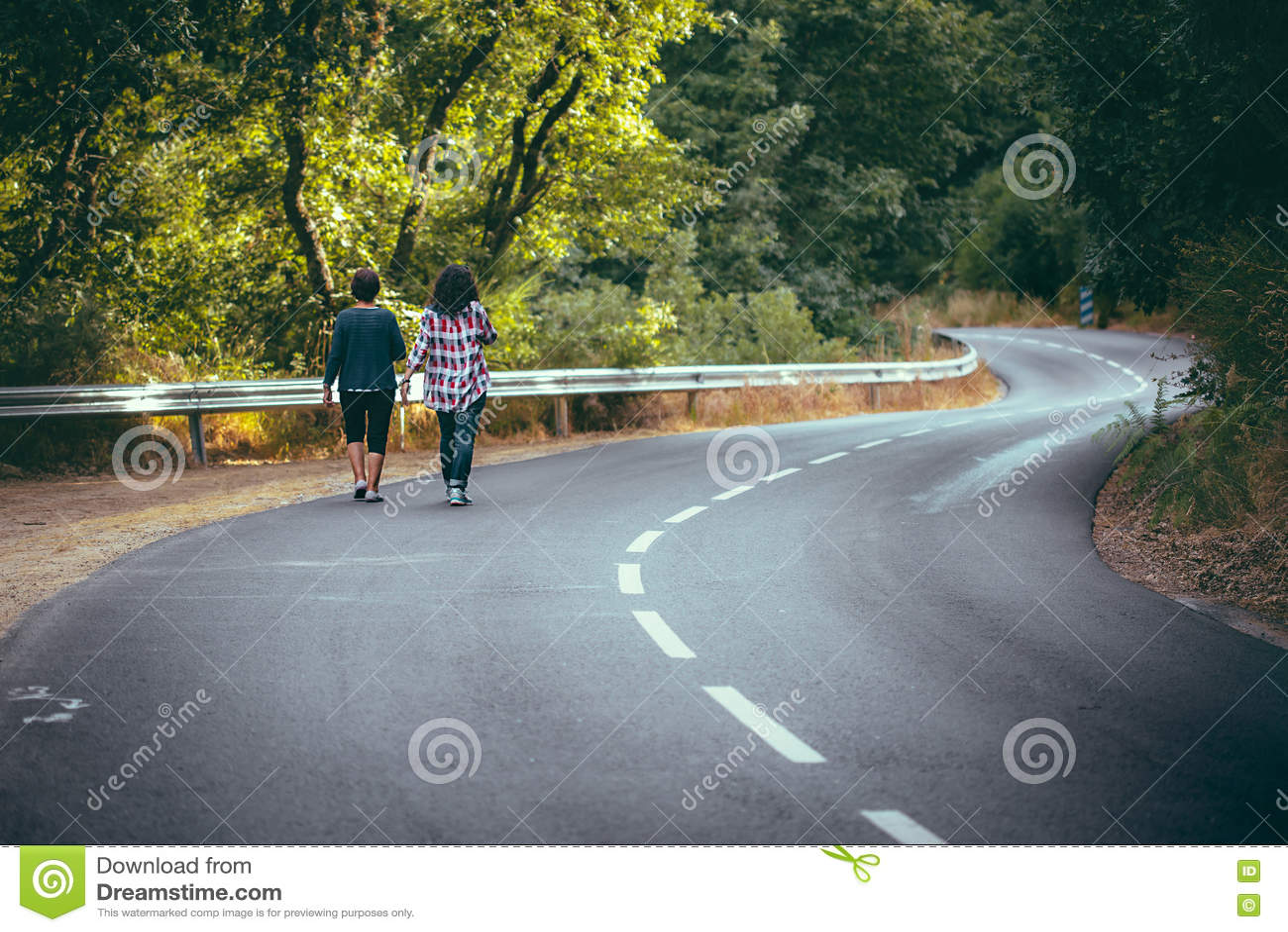 Kvinnor som går på härlig skog för väg korsningen