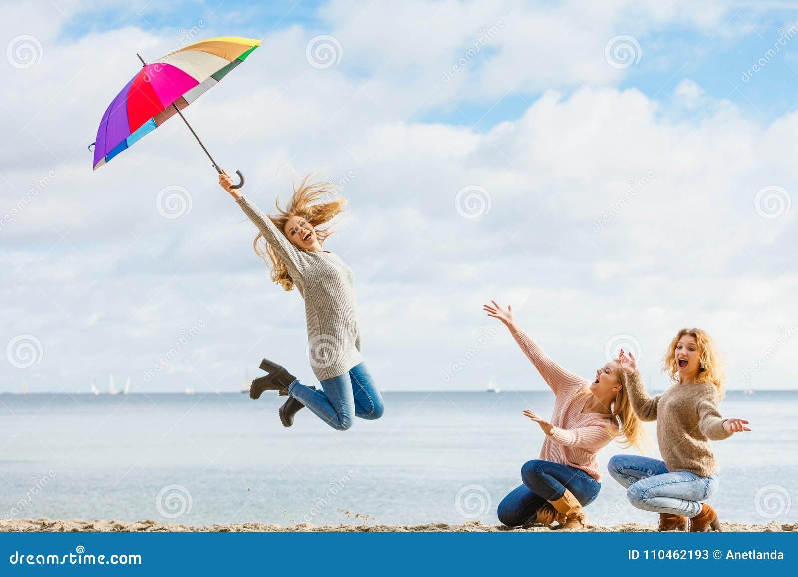 Kvinnor som hoppar med paraplyet