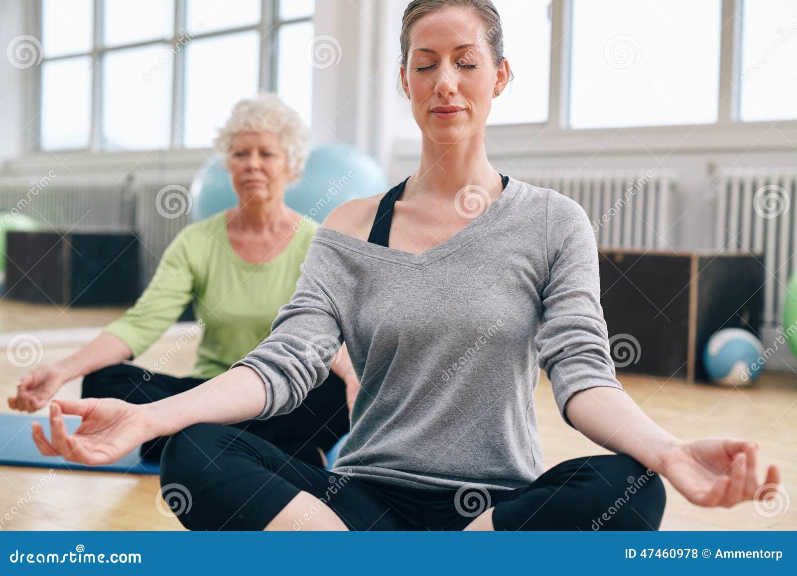 Kvinnor som kopplar av och mediterar i deras yogagrupp på idrottshallen