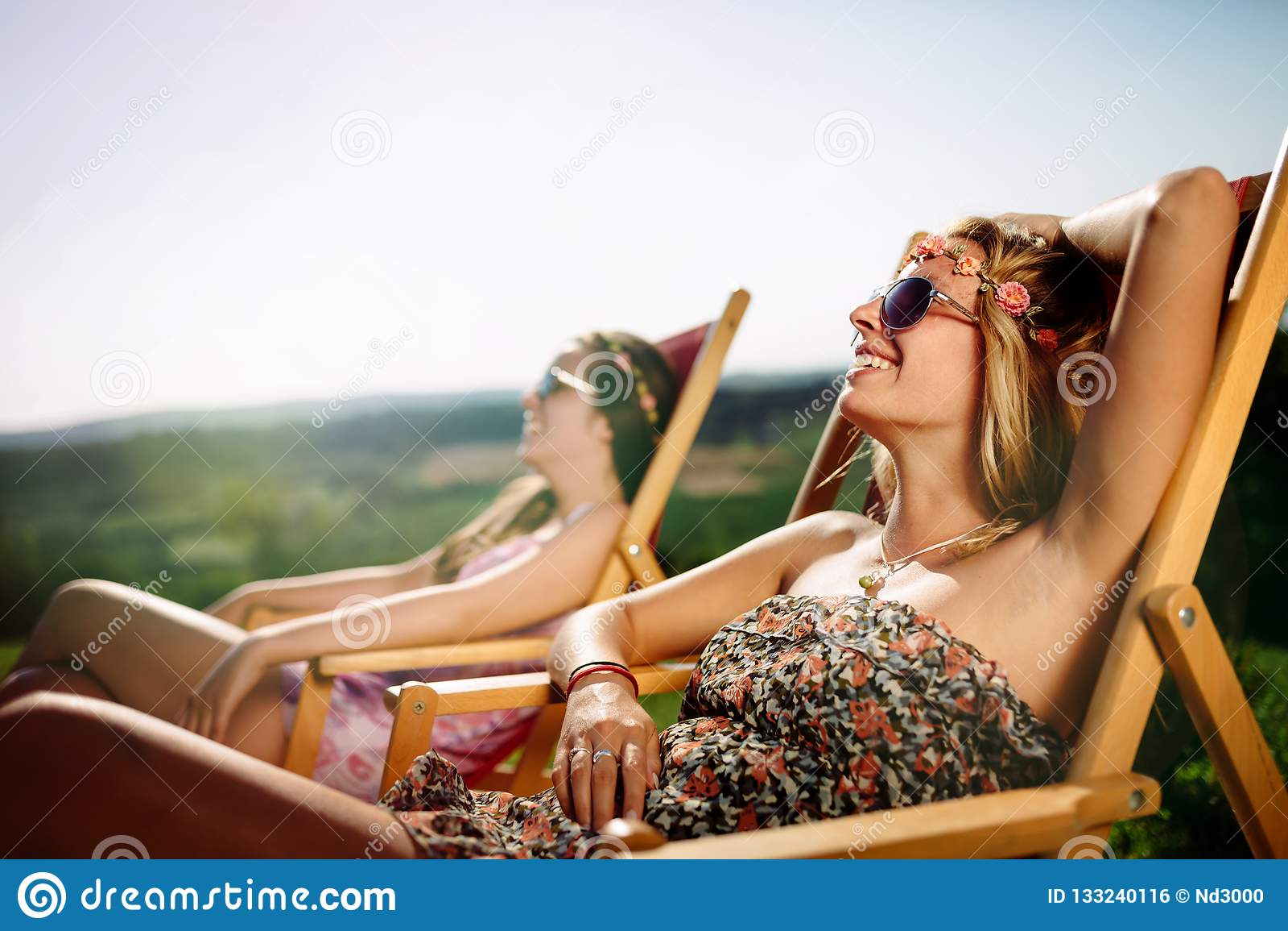 Kvinnor som kopplar av och solbadar i sommar