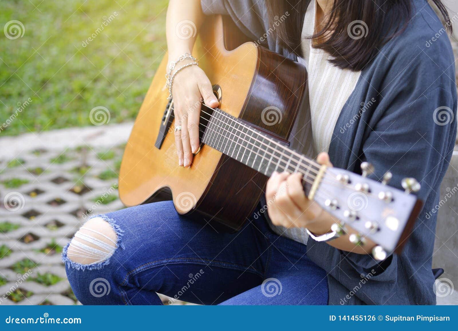 Kvinnor som spelar den akustiska gitarren i trädgården