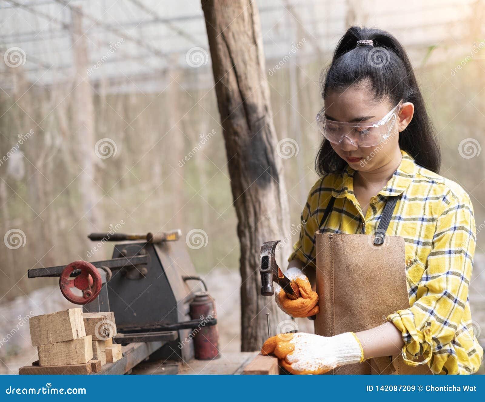 Kvinnor som står byggmästaren som bär den kontrollerade skjortaarbetaren av att bulta för konstruktionsplats, spikar i det trä