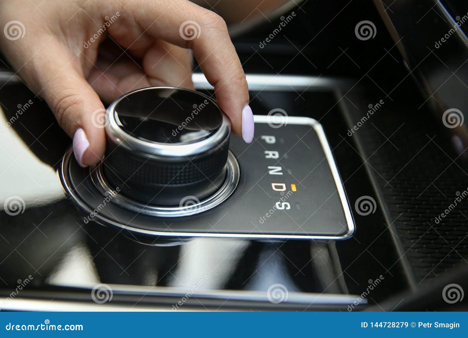 Kvinnors hand inkluderar ett drevfunktionsläge på närbilden för den automatiska överföringen