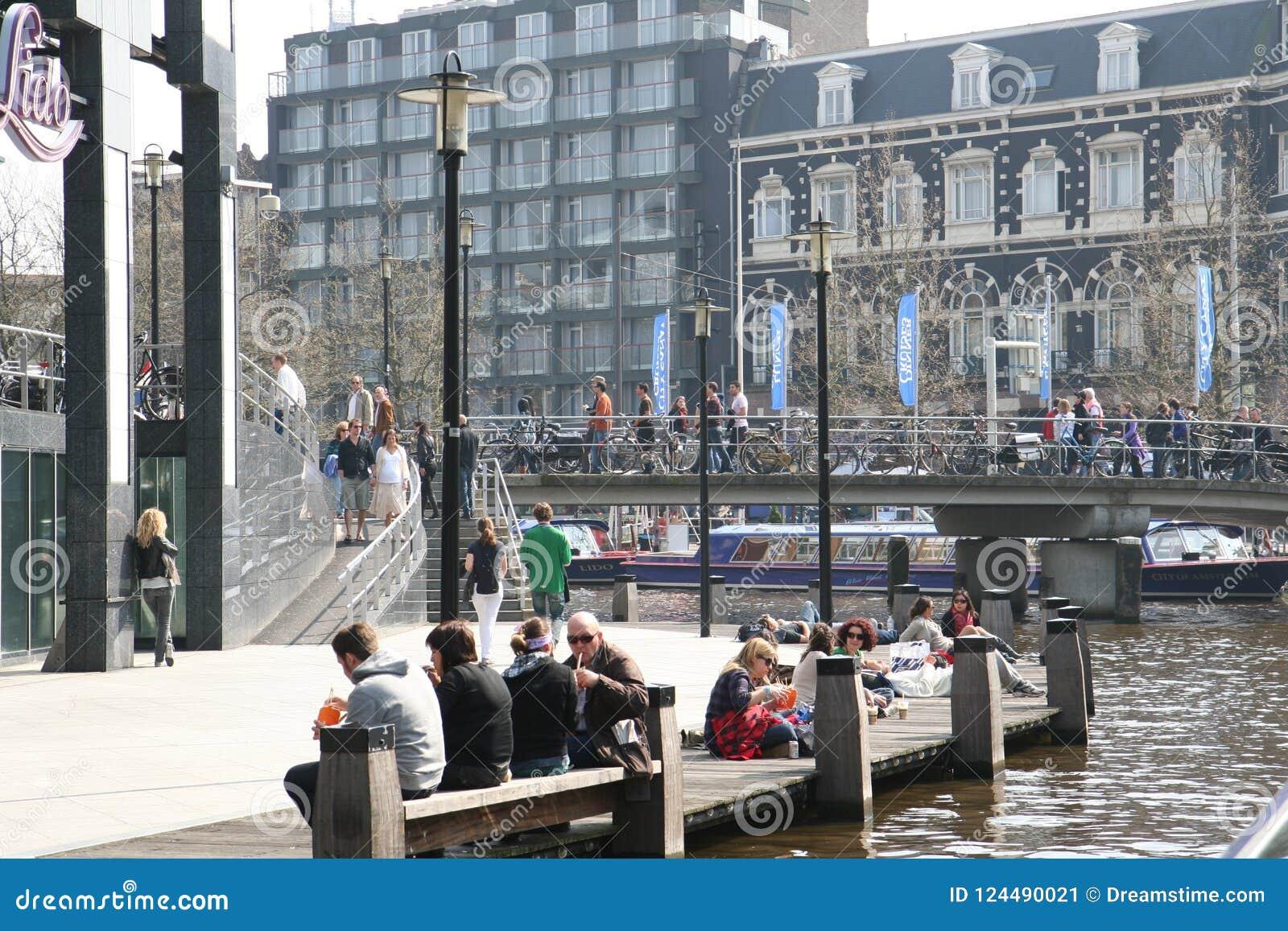 Kwadrat w mieście Ludzie relaksują blisko wody i w kawiarni Ciepły dzień w mieście