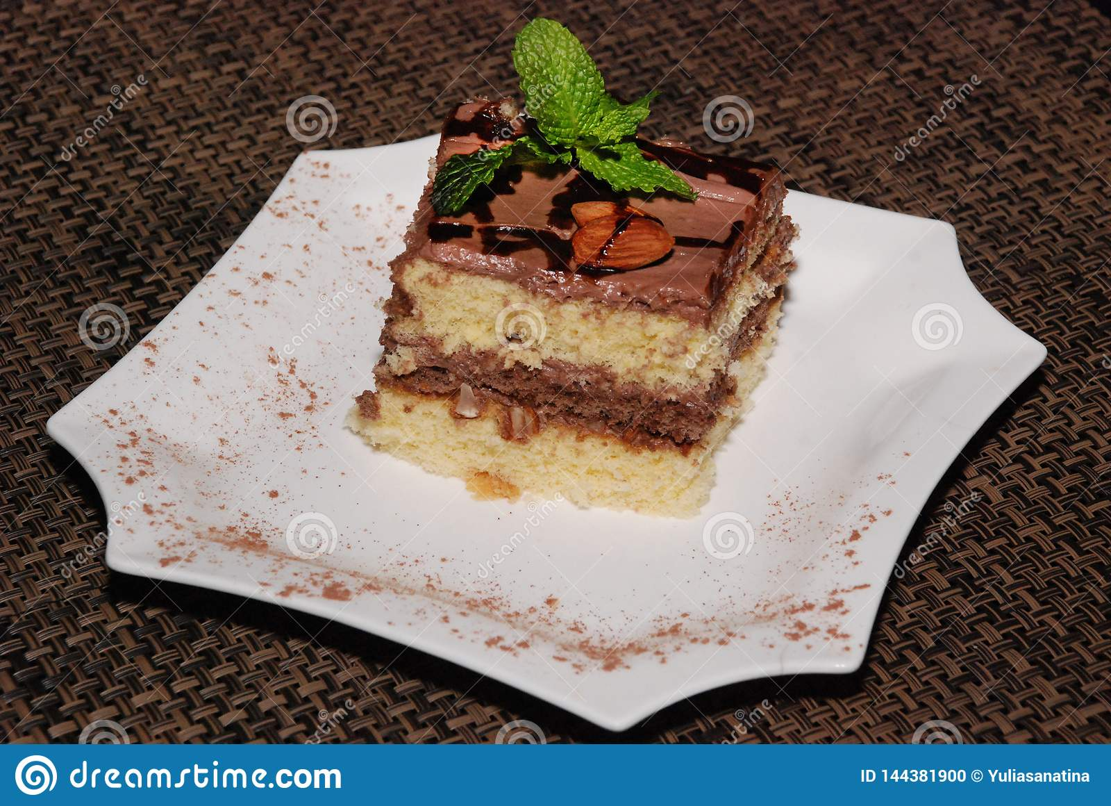 Kwadratowy kawałek tort z czekoladą i migdałem na białym talerzu