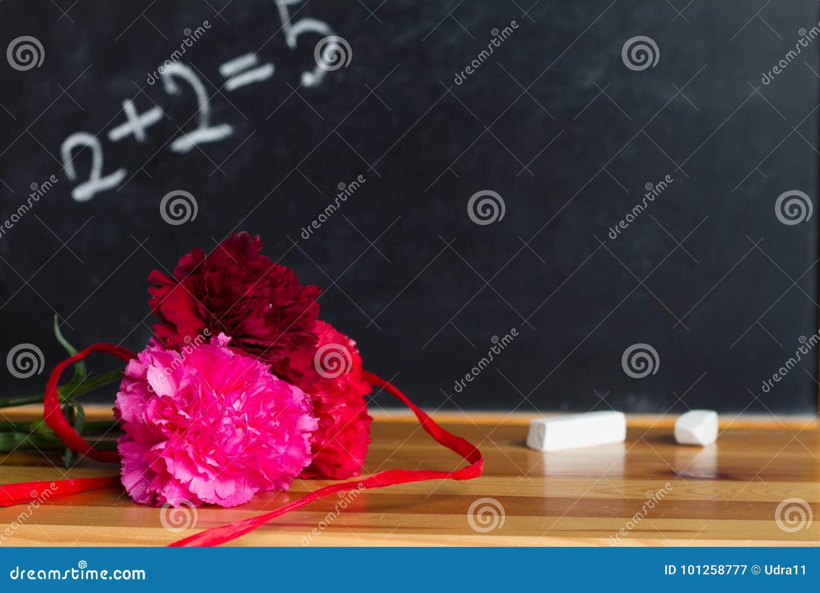 Kwiaty i blackboard w sala lekcyjna nauczyciela dnia tła pojęciu