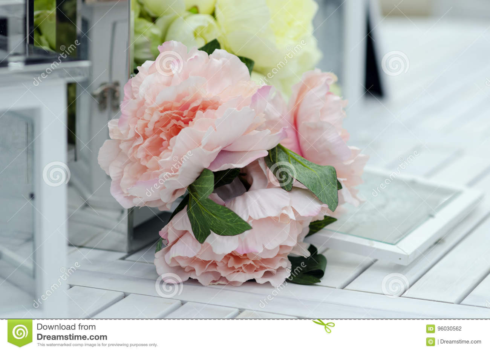 Kwiaty i lampy na białym drewnianym stole