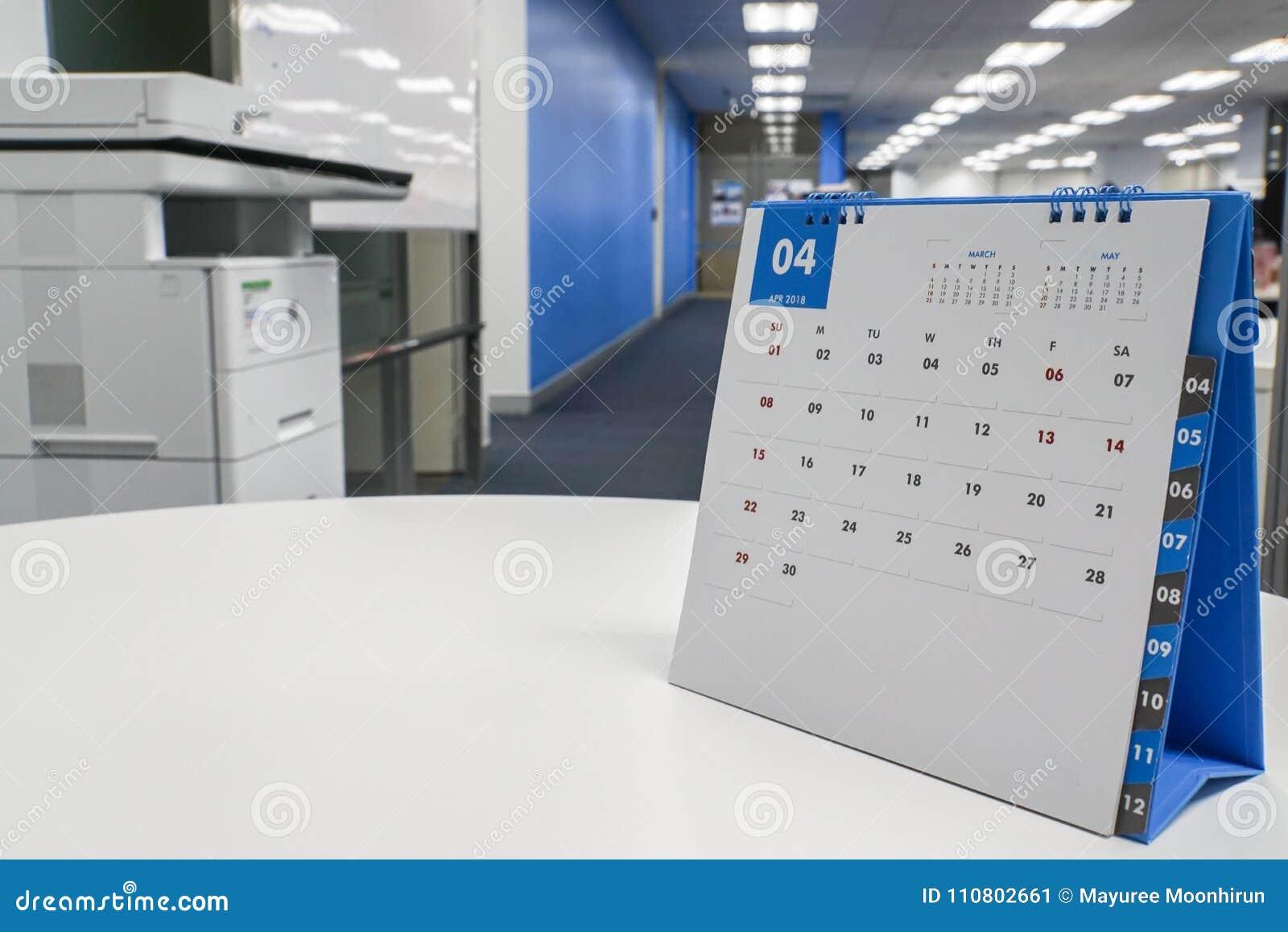 Kwietnia kalendarz 2018 na biurku z biurowym tłem