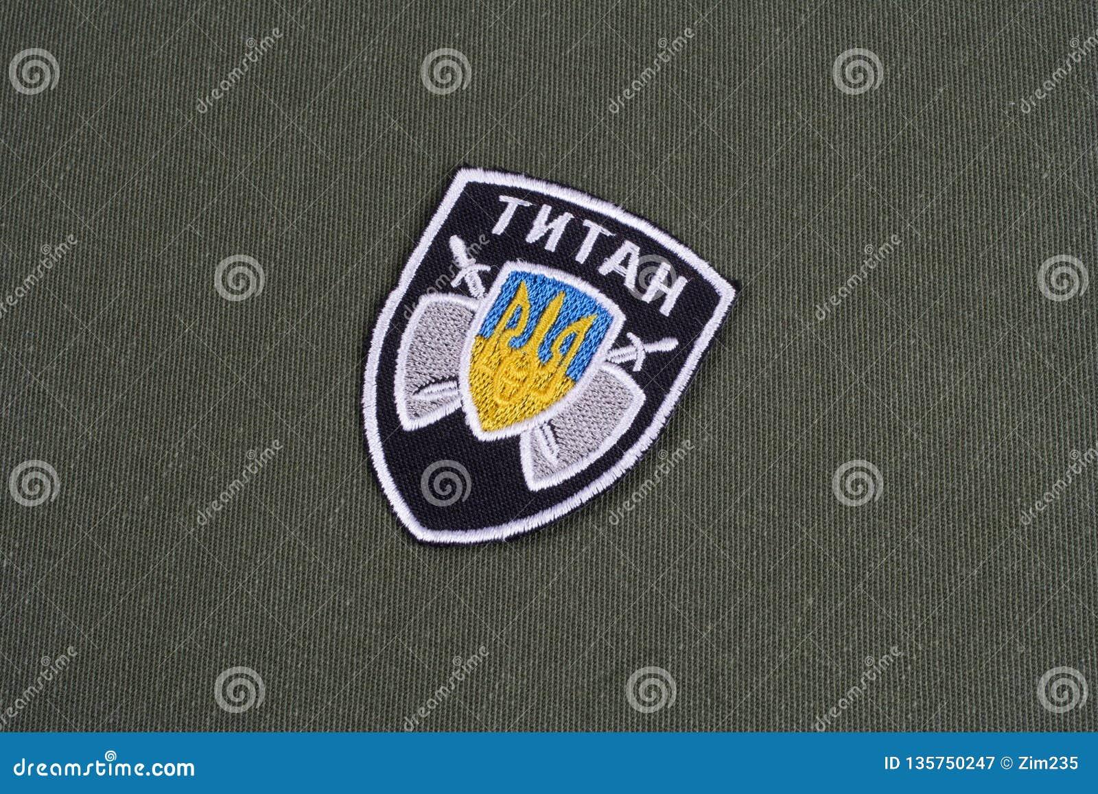 KYIV, УКРАИНА - 16-ое июля 2015 Министерство внутренних дел (Украины) - значок блока титана равномерный на закамуфлированной форм