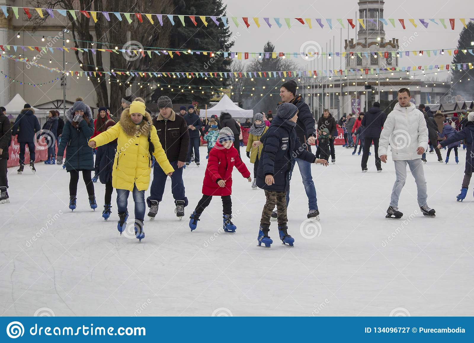 Kyiv de Oekraïne - 01 01 2018: gelukkige mensen die bij de piste op de de wintervakantie schaatsen