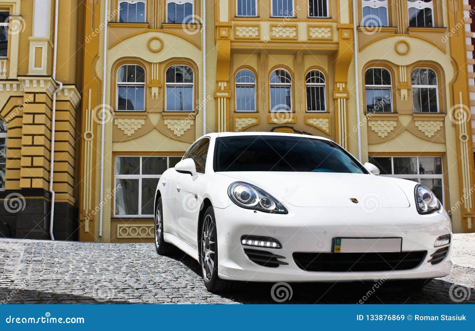 Kyiv, de Oekraïne, 25 Juni, 2015; Wit Porsche Porsche Panamera op de achtergrond van mooie gebouwen