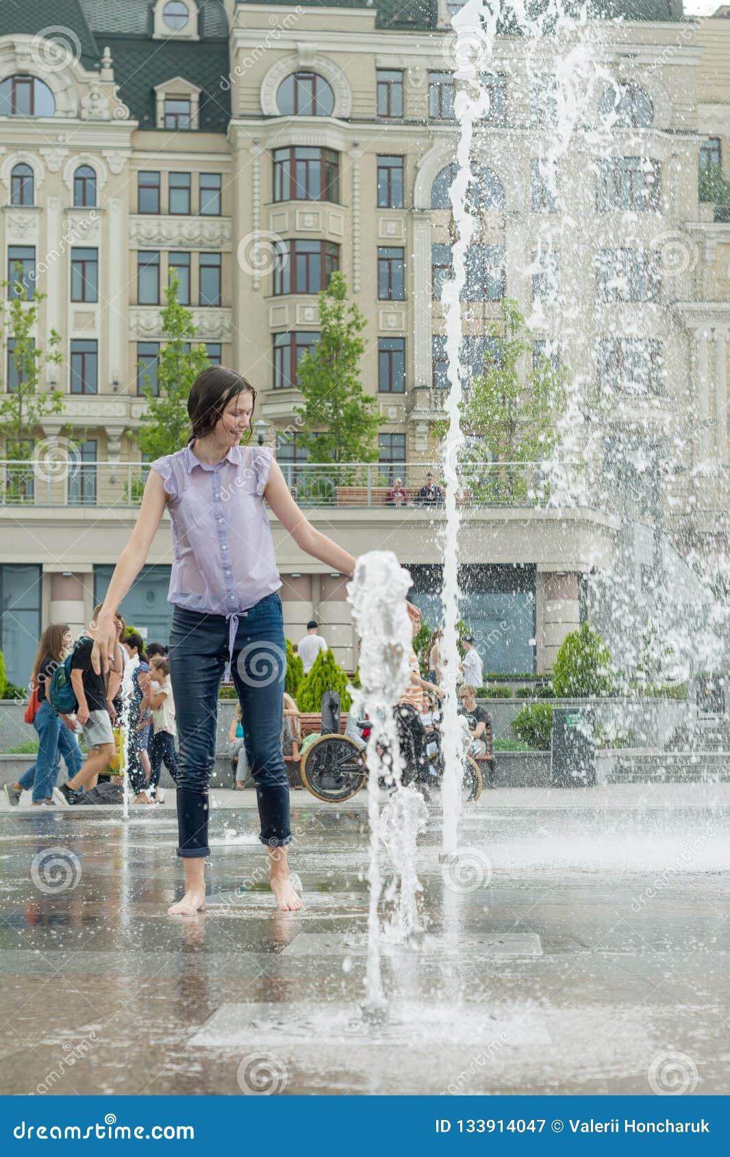 Kyiv UA, 19-07-2018 城市喷泉的快乐的青少年女孩,湿衣裳的女孩获得乐趣并且享受凉快的夏天