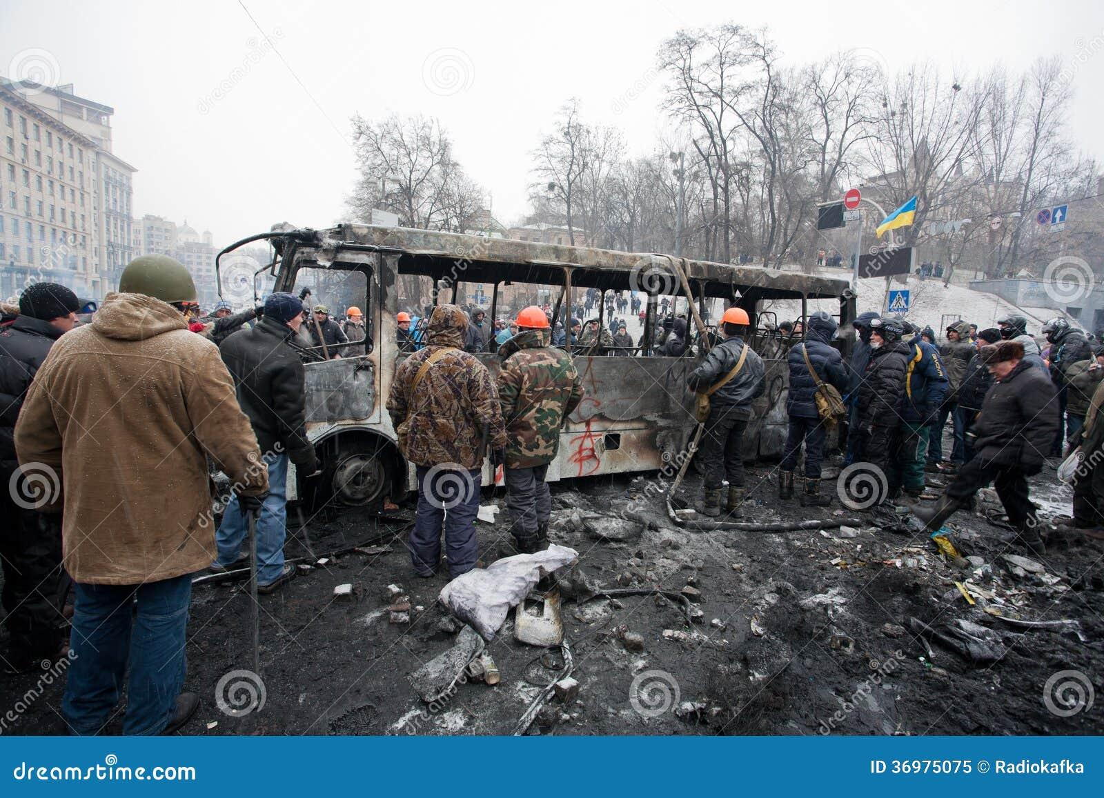 KYIV, UCRAINA: Molti uomini in uniforme ed in caschi hanno capovolto il bus bruciato sulla via d occupazione durante la protesta a
