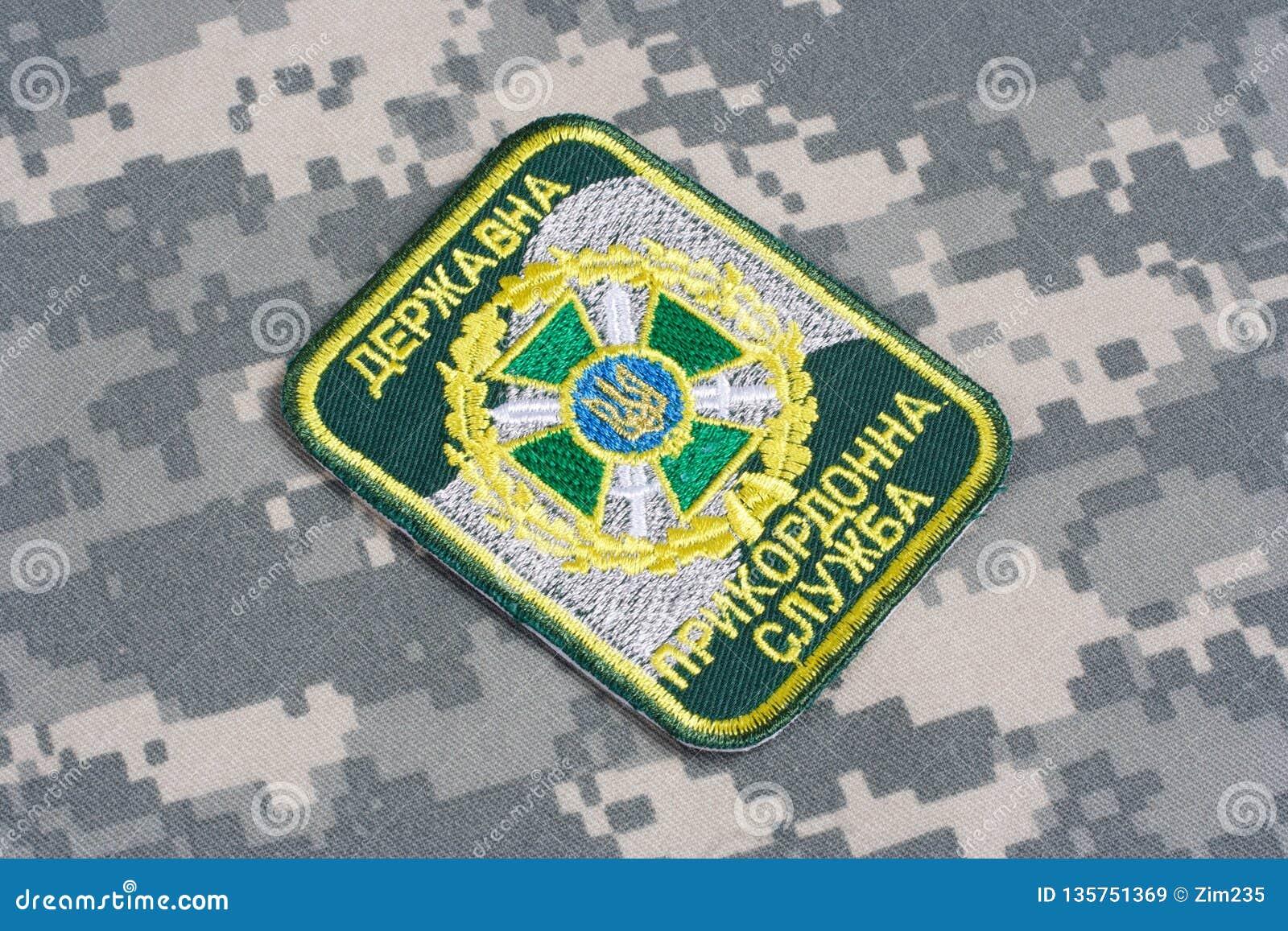 KYIV UKRAINA - Juli, 16, 2015 Enhetligt emblem för Ukraina gränsbevakning på den kamouflerade likformign