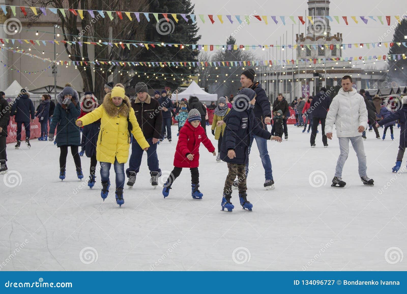 Kyiv Ukraina - 01 01 2018: lyckligt folk som åker skridskor på isbanan på vinterferierna