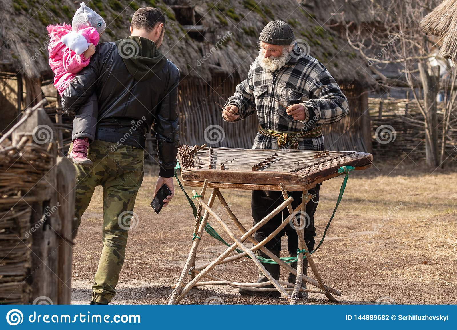 Kyiv UKRAINA - MARS 08, 2019: Mässa av folkkonst i Pirogovo En gråhårig skäggig farfar i gården av ett gammalt traditionellt