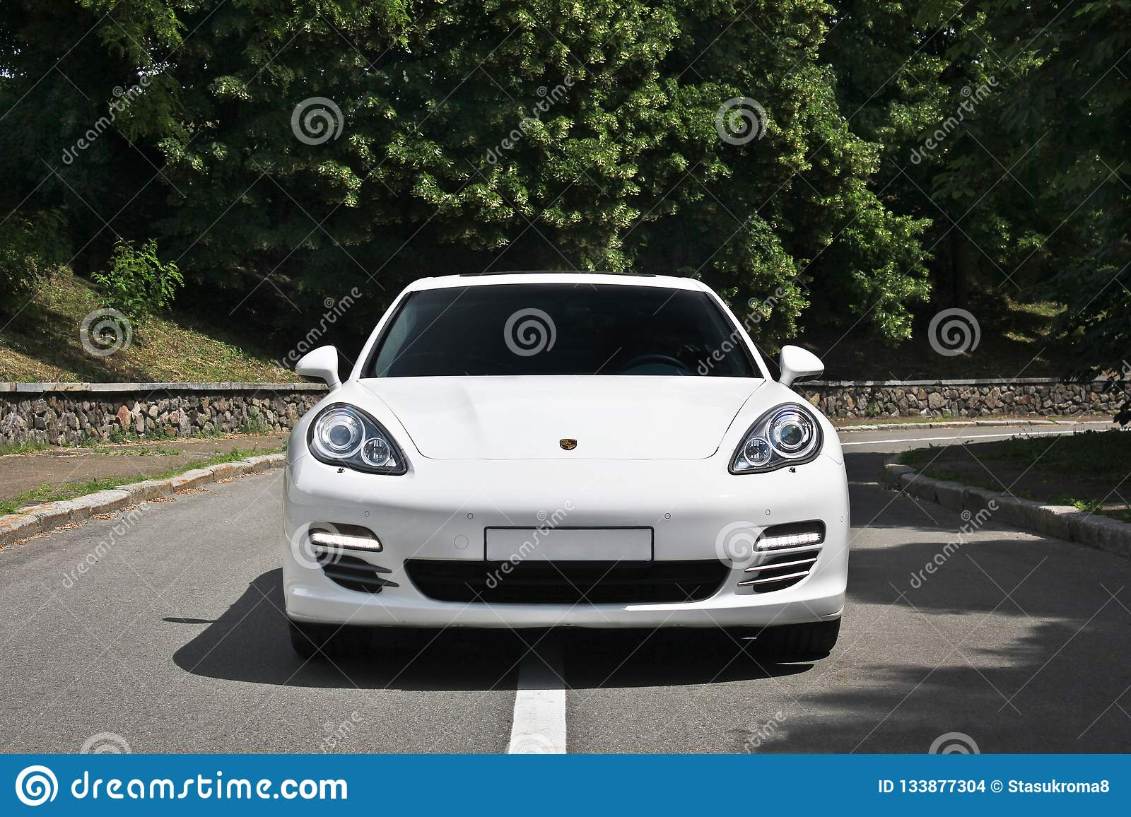 Kyiv, Ukraine, June 25, 2015; White Porsche. Porsche Panamera on the background of trees