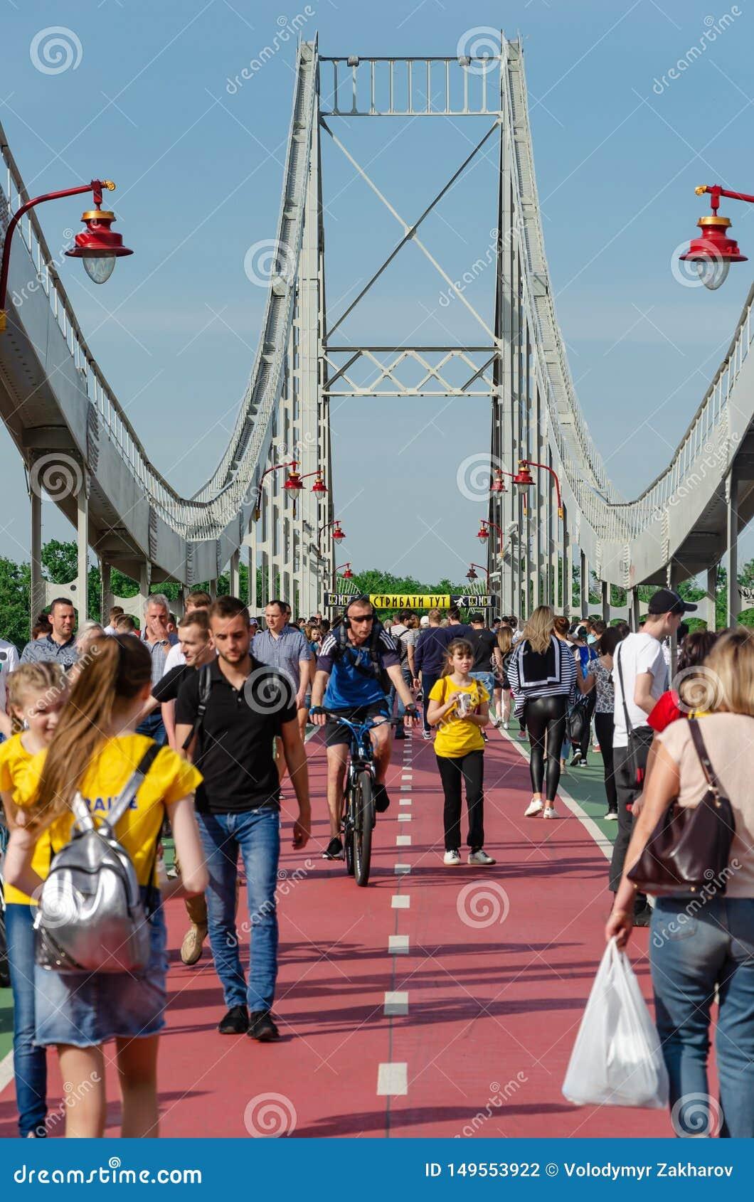 Kyiv, Ukraine - May 18, 2019. Park bridge over the Dnipro river. People walking along the pedestrian bridge on weekend