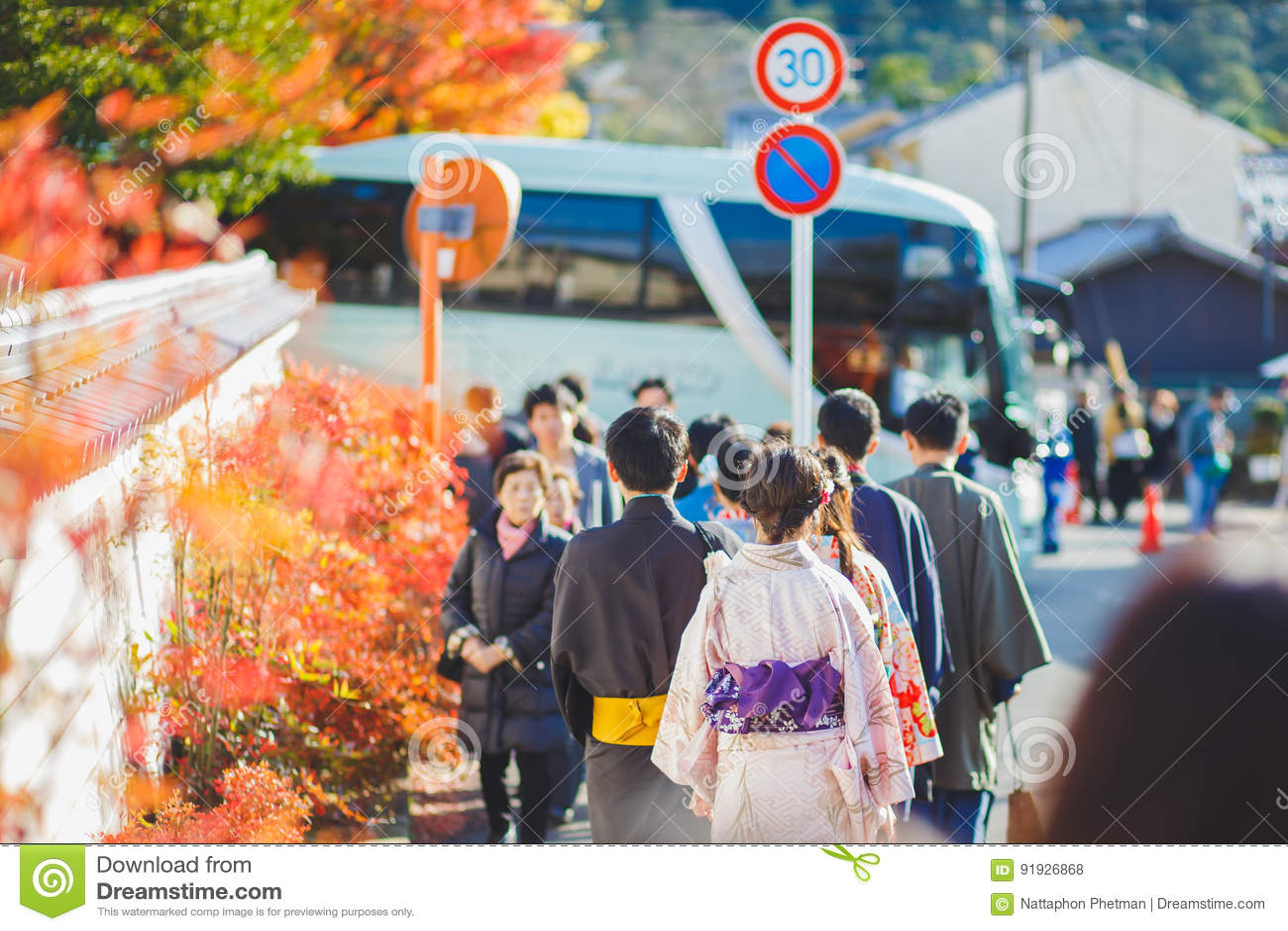 KYOTO, GIAPPONE - 23 novembre 2016 acero rosso, uomo e donne di autunno facenti attenzione al yukata ed al kimono camminanti sull
