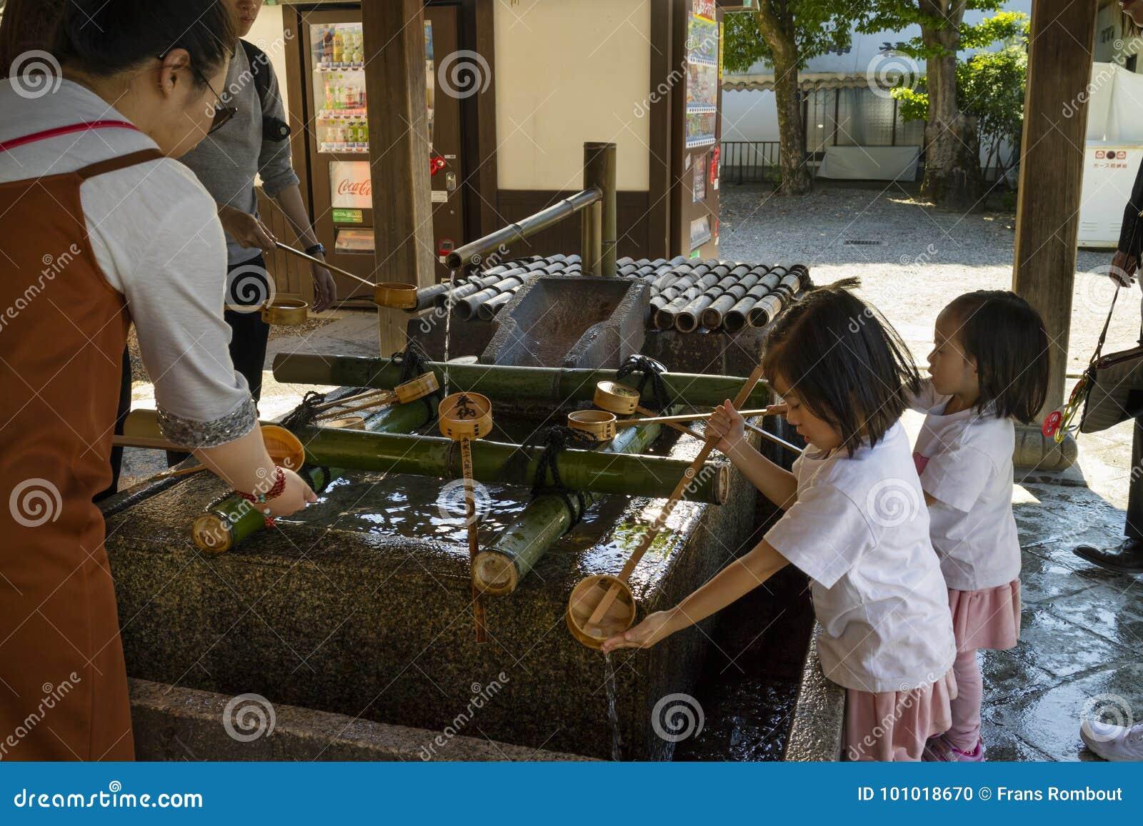 Kyoto, Japón - 18 de mayo de 2017: Niños que limpian sus manos en a