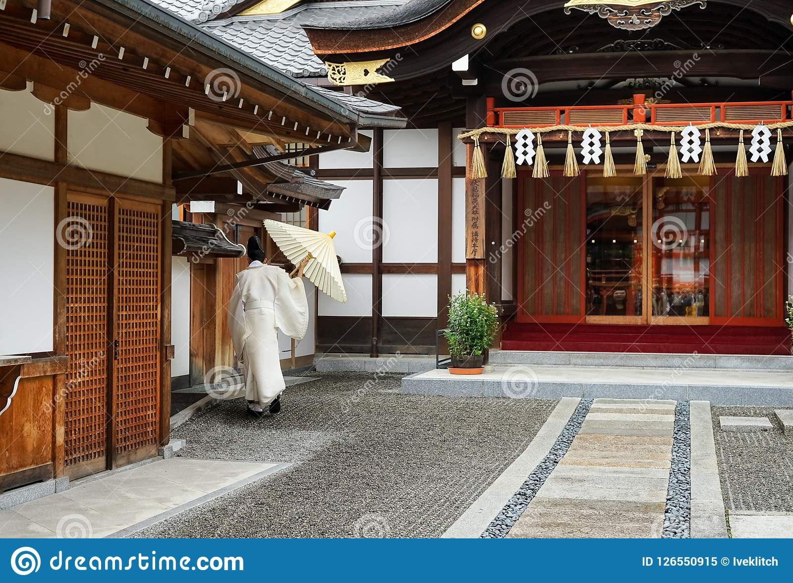 Japanese monk in white dress from behind on outdoors in temple Kyoto