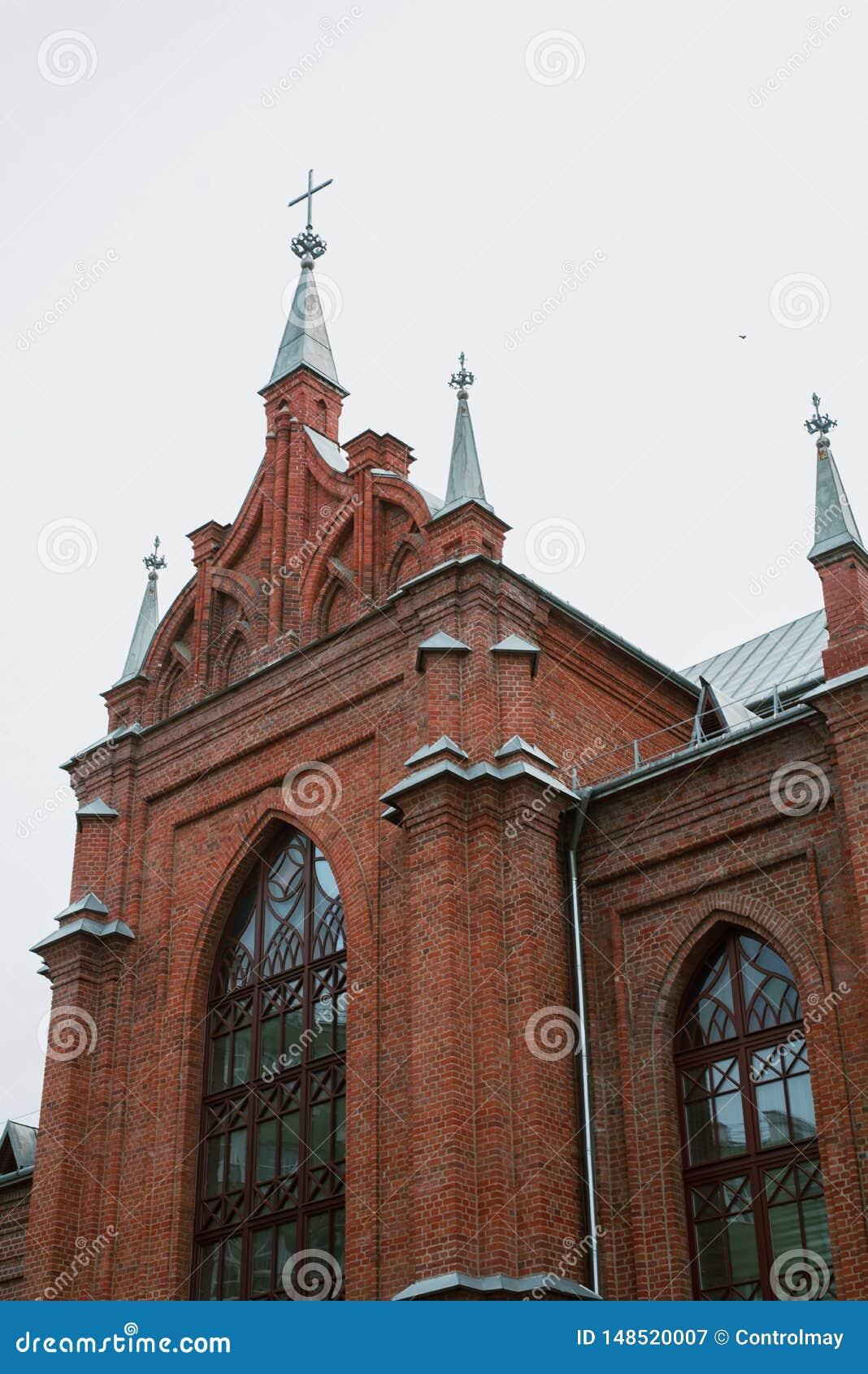 Kyrkan är av röd tegelsten, med kors och tunna fönster