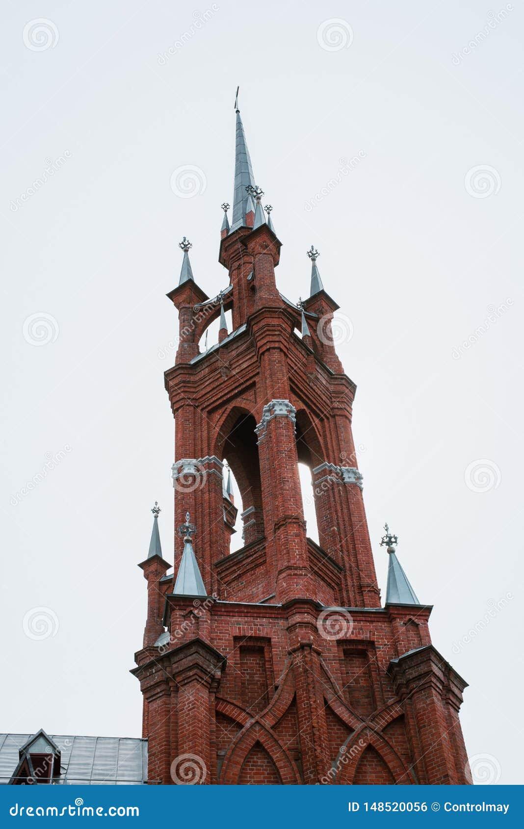 Kyrkan ?r av r?d tegelsten, med kors och tunna f?nster
