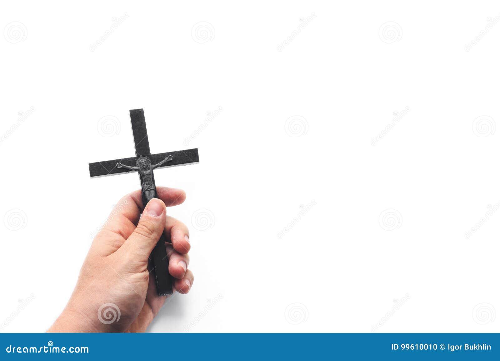 Kyrkliga redskap Man som rymmer ett kors Closeupen av träkristenkorset i handen på viten isolerade bakgrund