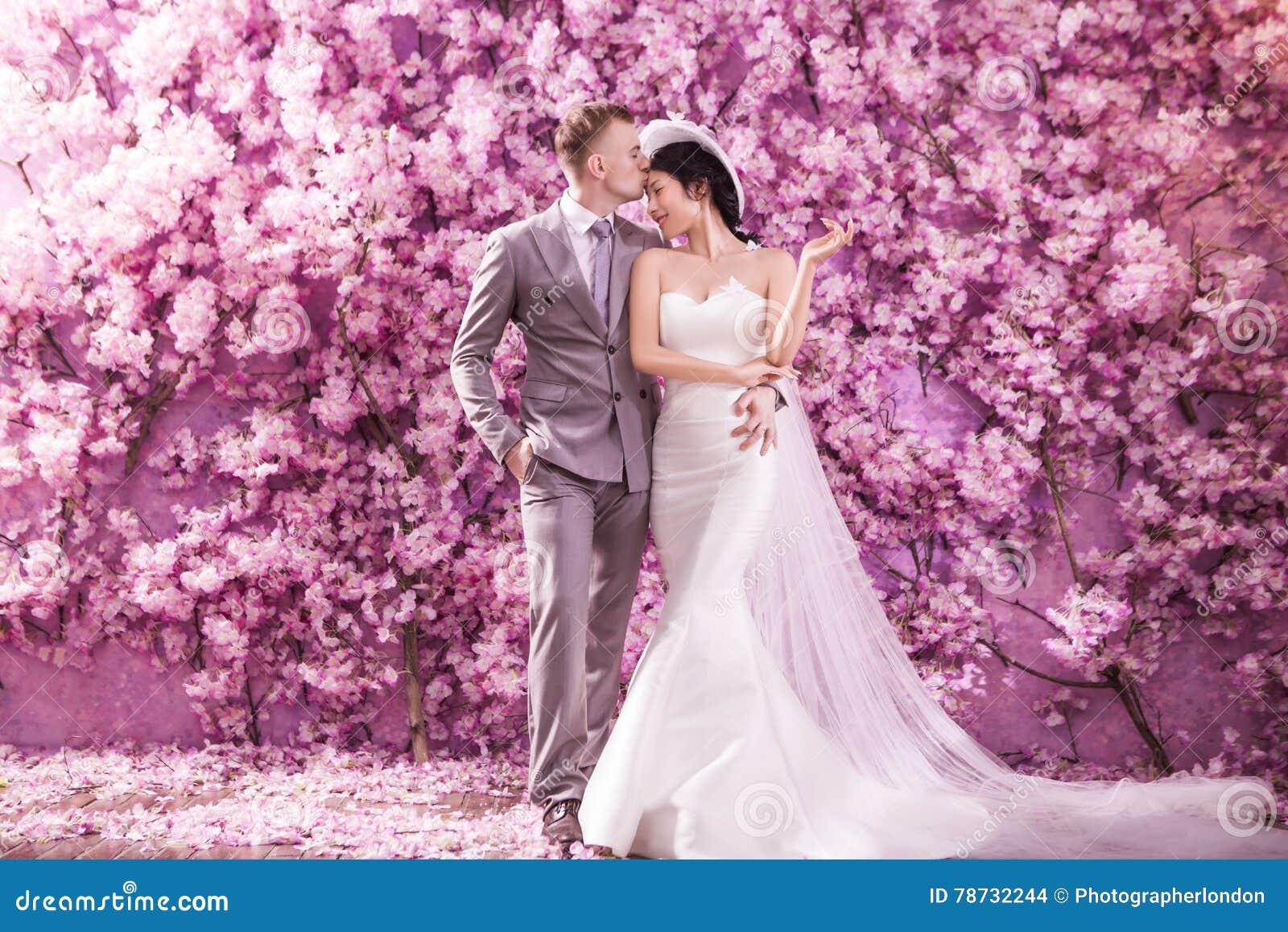 Kyssande brud för romantisk brudgum på pannan, medan stå mot väggen som täckas med rosa blommor