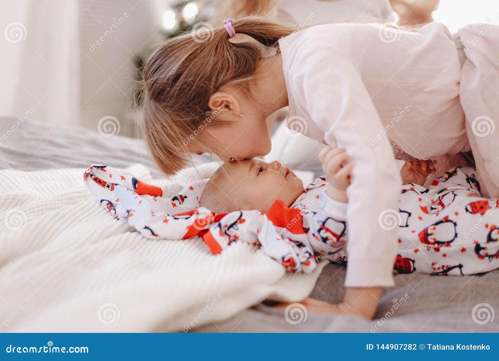 Kysser den iklädda pajamaen för lilla flickan hennes mycket lilla broder som ligger på sängen
