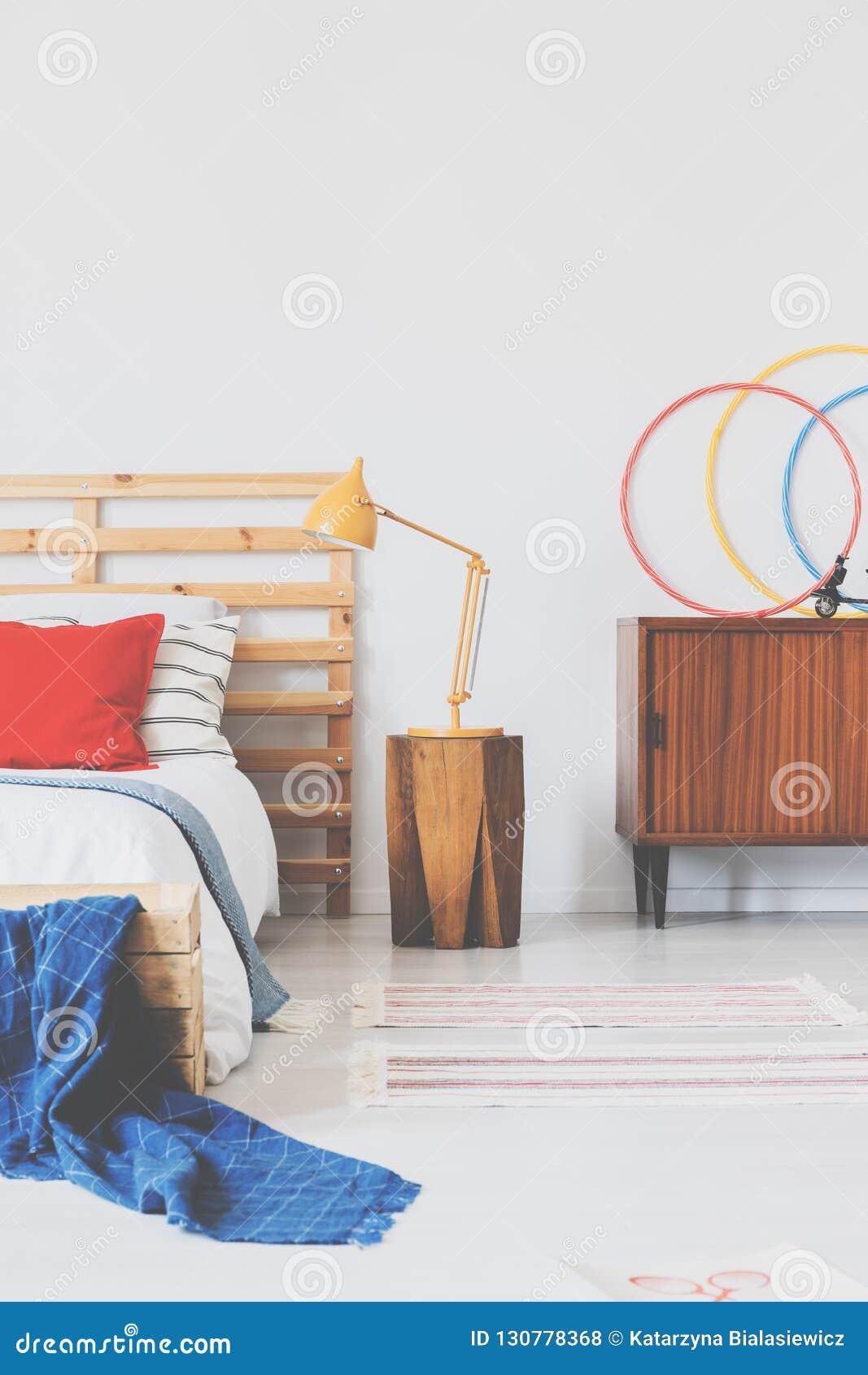 Lámpara anaranjada en la mesita de noche de madera al lado de la cama cómoda con la almohada roja y el cabecero elegante en inter