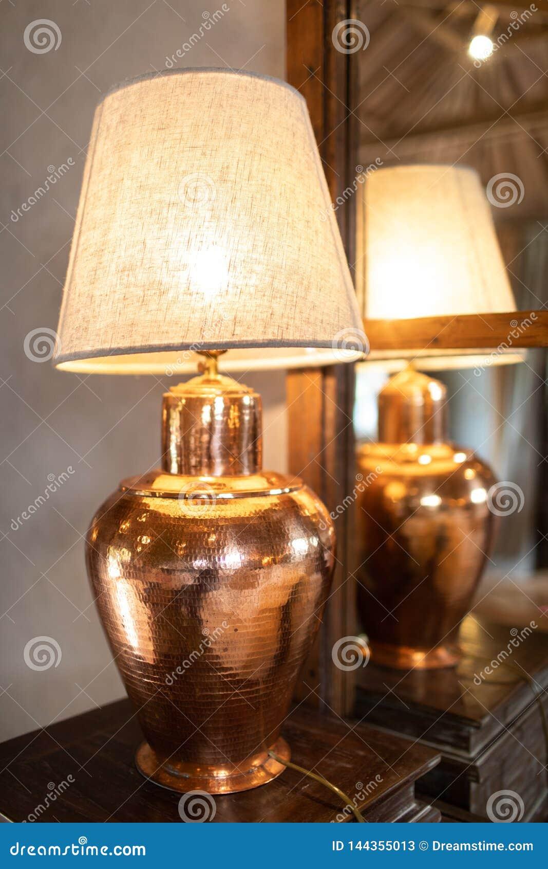 Lámpara de bronce en la tabla de madera