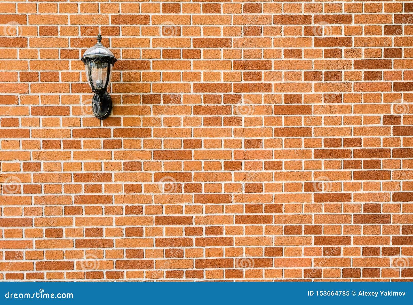 Lámpara de pared del vintage en una pared de ladrillo decorativa rojo-anaranjada y marrón
