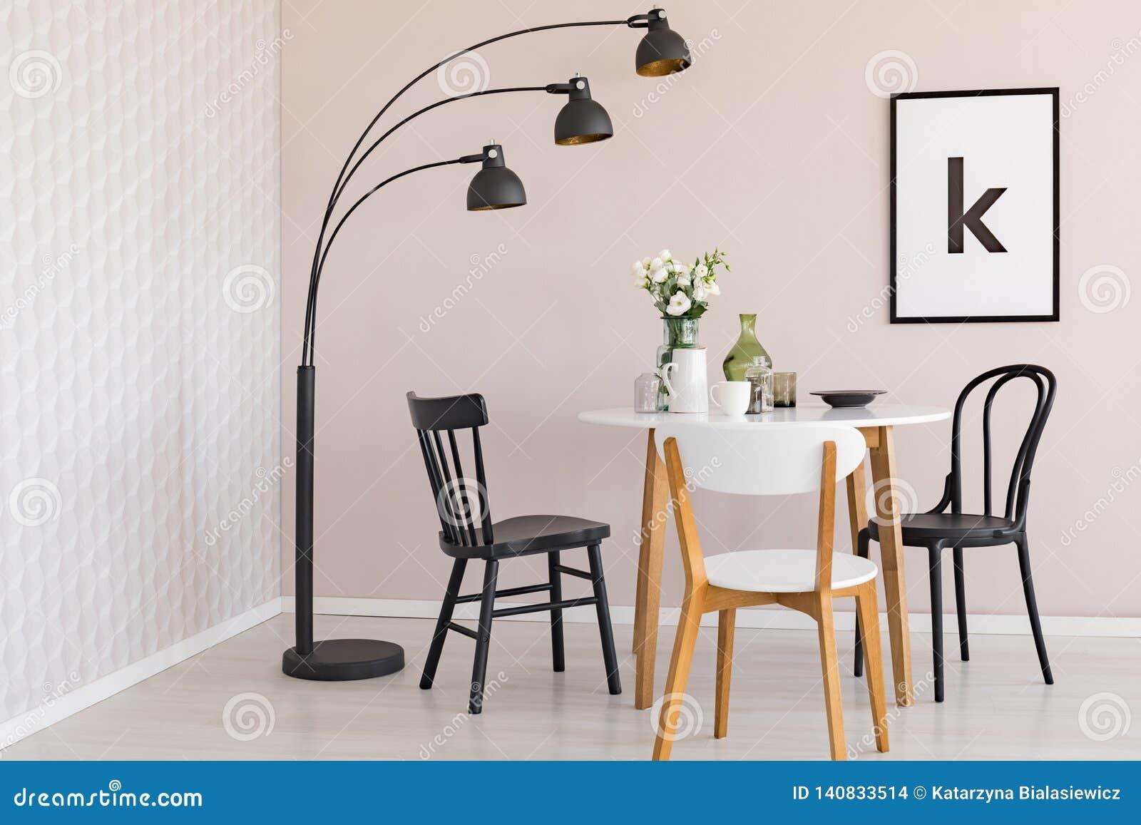 Lámpara negra sobre sillas y tabla de madera con las flores en el comedor interior con el cartel Foto verdadera