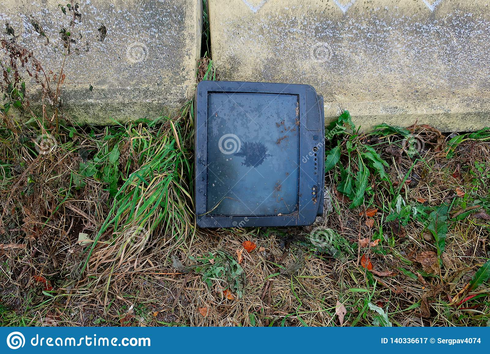 Lámpara vieja quebrada TV en el muro de cemento
