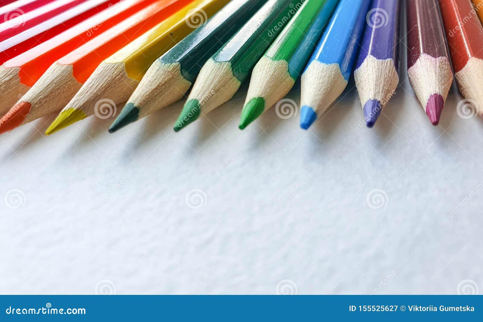 Lápices coloreados de madera, estilo del arco iris, en la hoja blanca del papel de dibujo con textura específica Copie el espacio