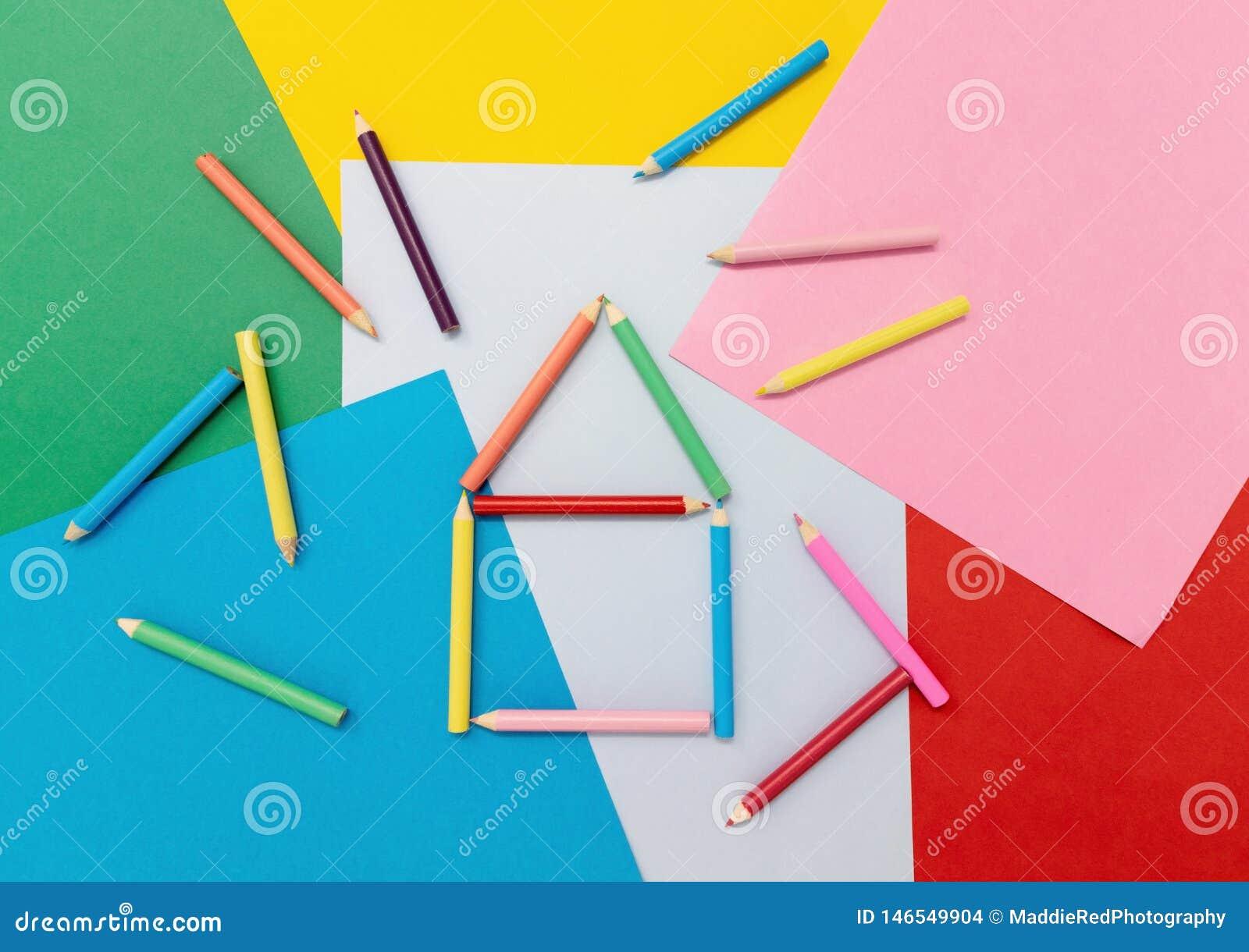 Lápices coloreados en la forma de una casa en el papel coloreado