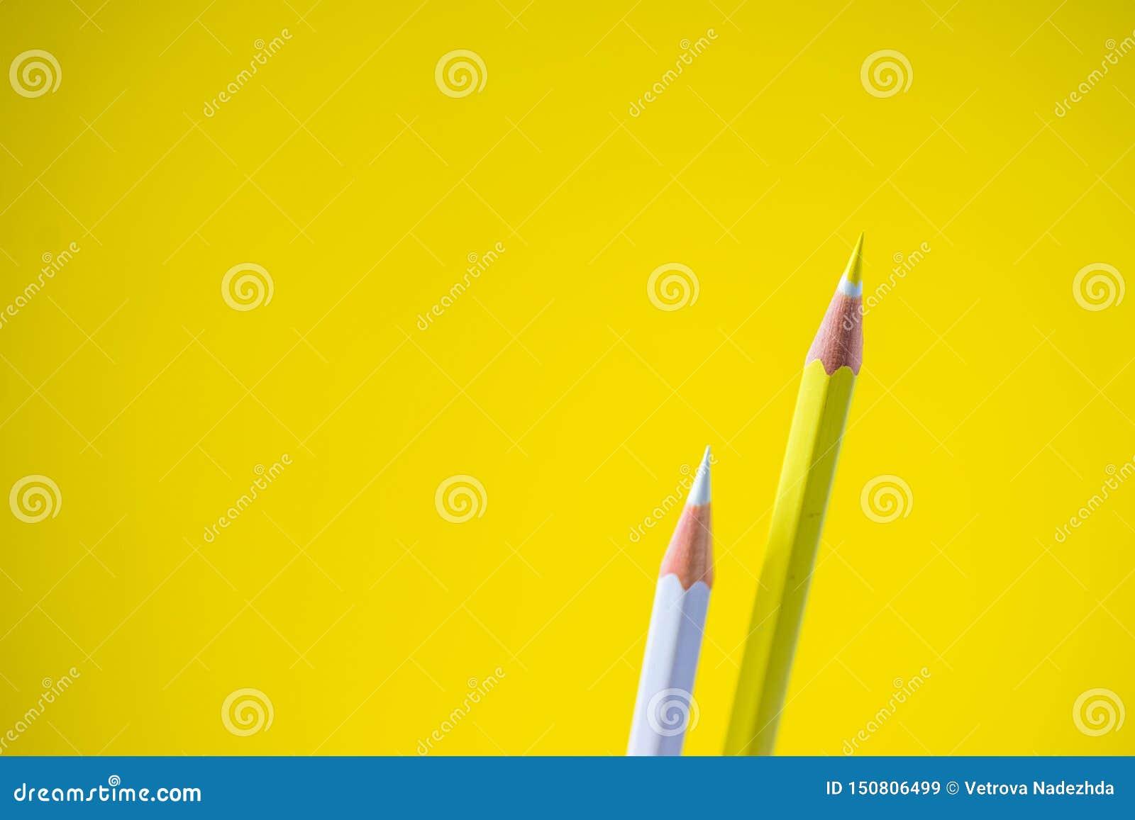 Lápices coloreados en un fondo amarillo con el espacio para el texto