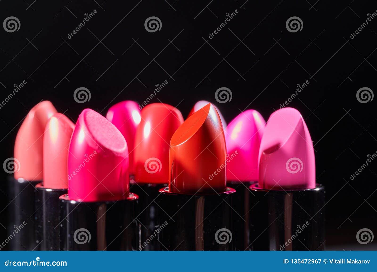 Lápices labiales coloridos de la moda sobre fondo negro Primer de los lápices labiales