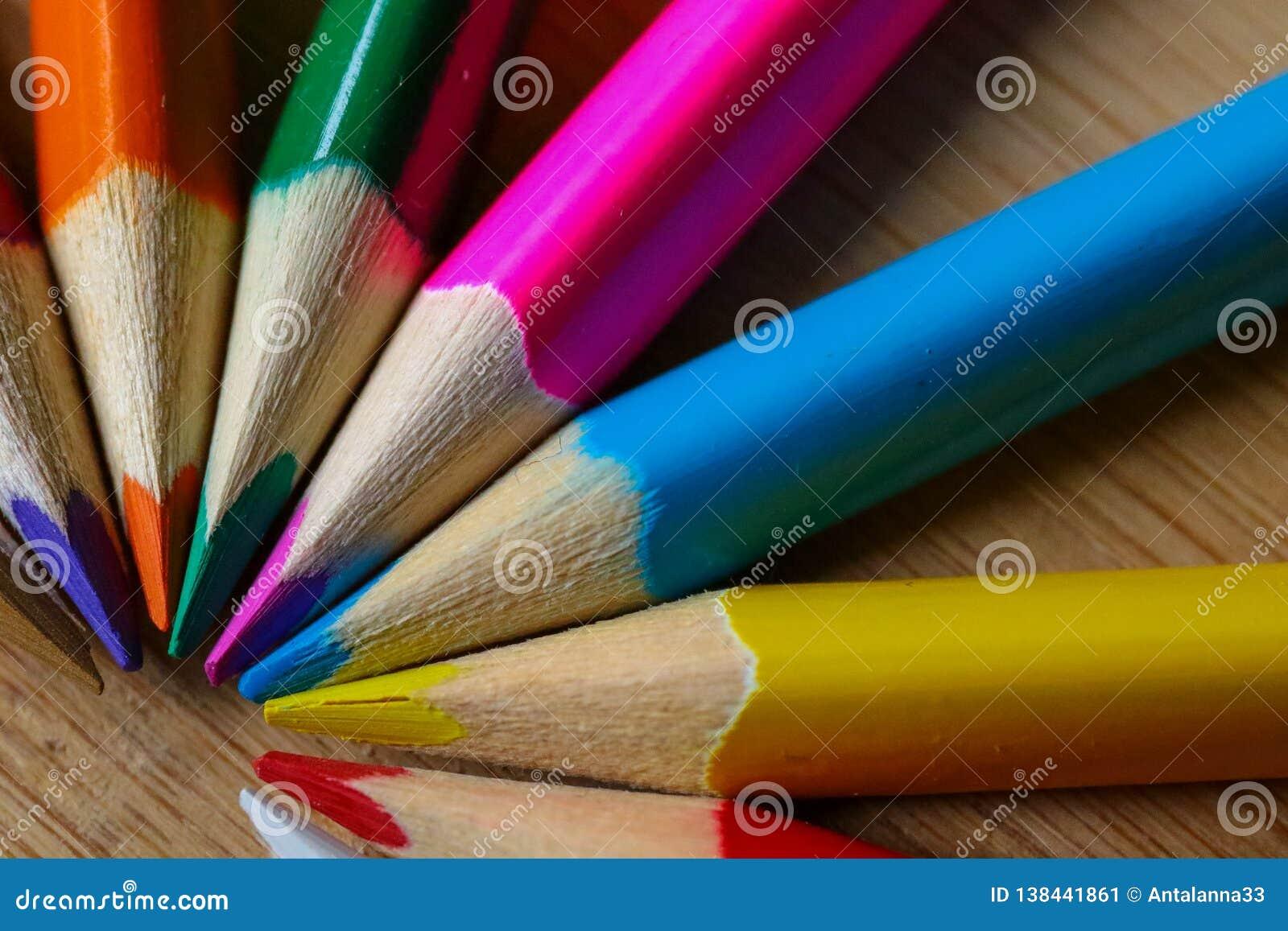 Lápices multicolores que forman un semi-círculo del color aislado en fondo de madera