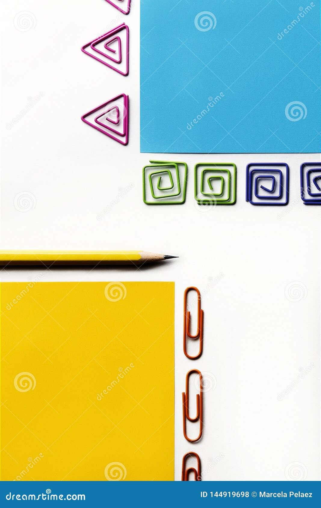 Lápis amarelo com papel azul e amarelo e os grampos coloridos de formas diferentes