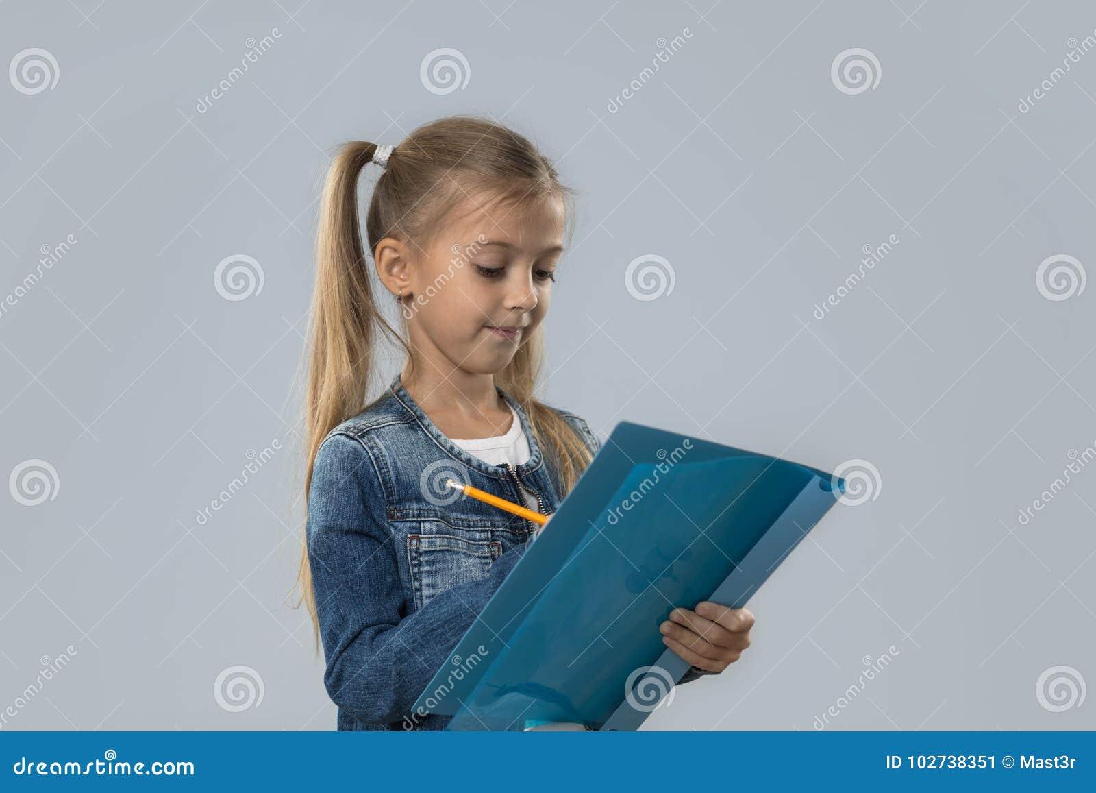 Lápis bonito da posse da menina que escreve o revestimento de sorriso feliz das calças de brim do desgaste isolado